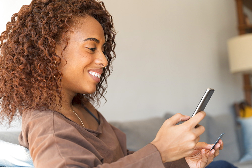 Smiling woman holding credit card and smart phone