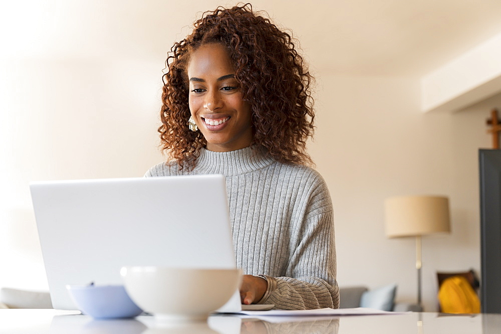 Smiling woman working on laptop at home