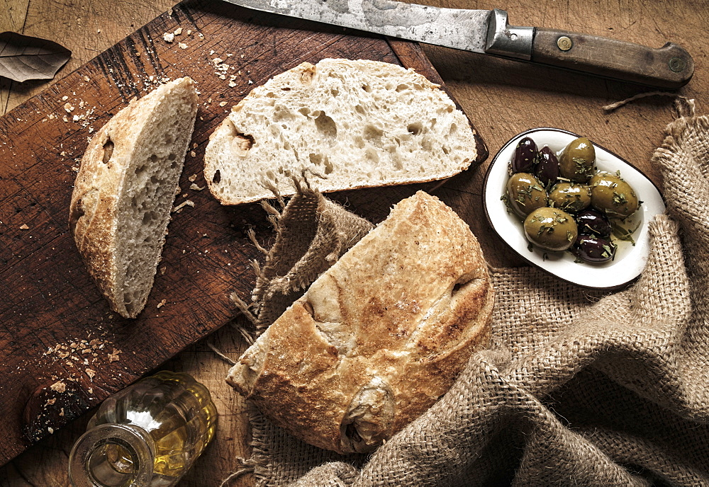 Sliced bread on cutting board by plate of olives