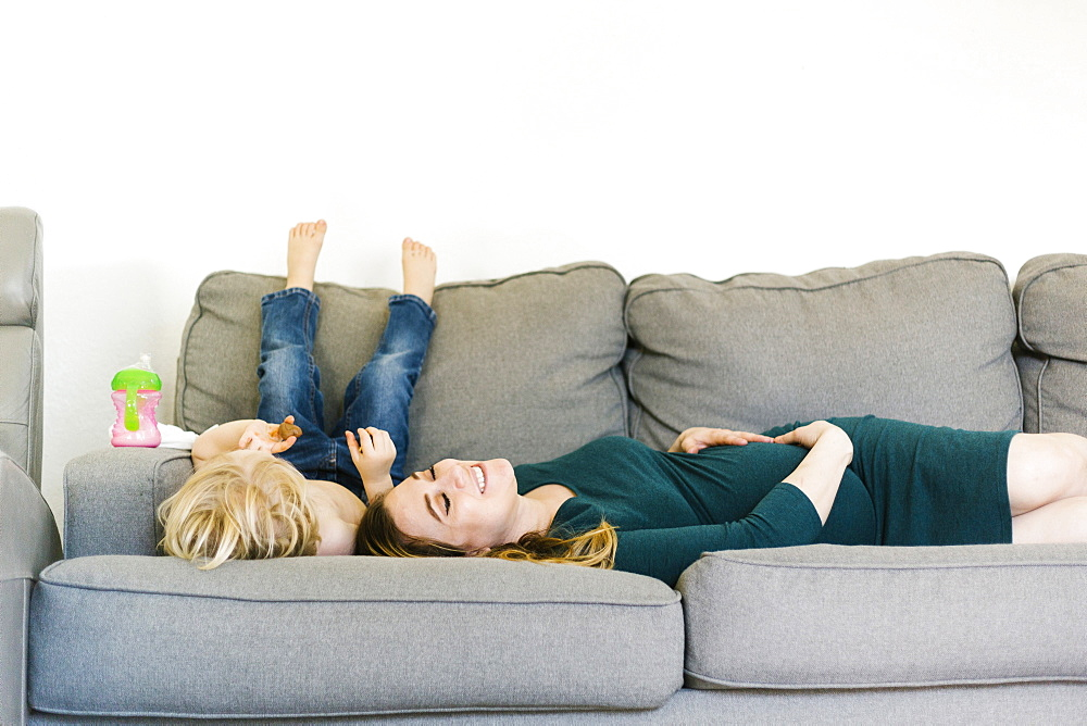 Pregnant woman lying on couch with son (4-5)