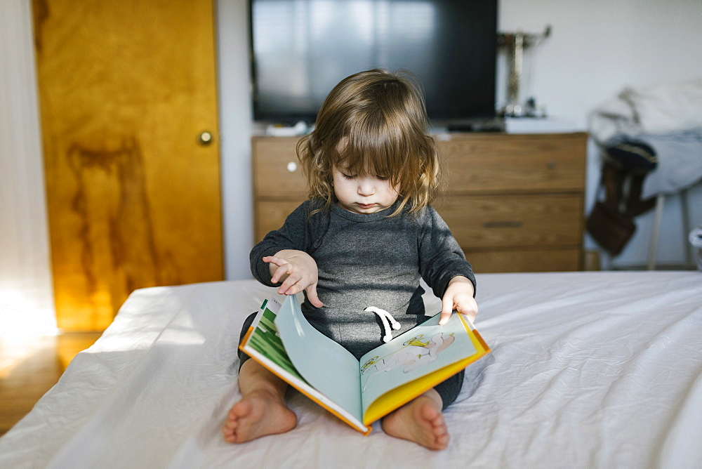 Girl (2-3) reading book on bed