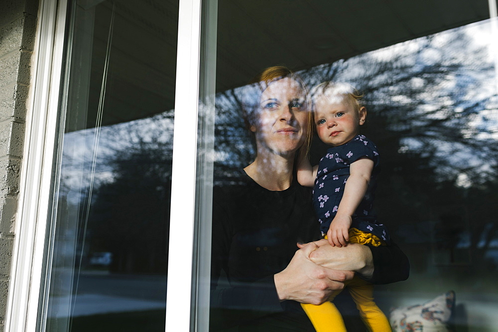 Mother holding daughter (2-3) and looking through window