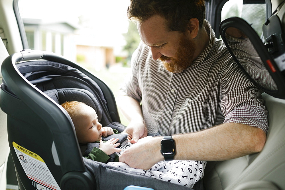 Father buckling baby boy (2-3 months) in car seat