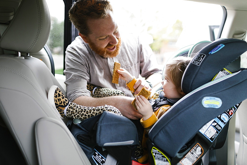 Father buckling daughter (2-3) in car seat