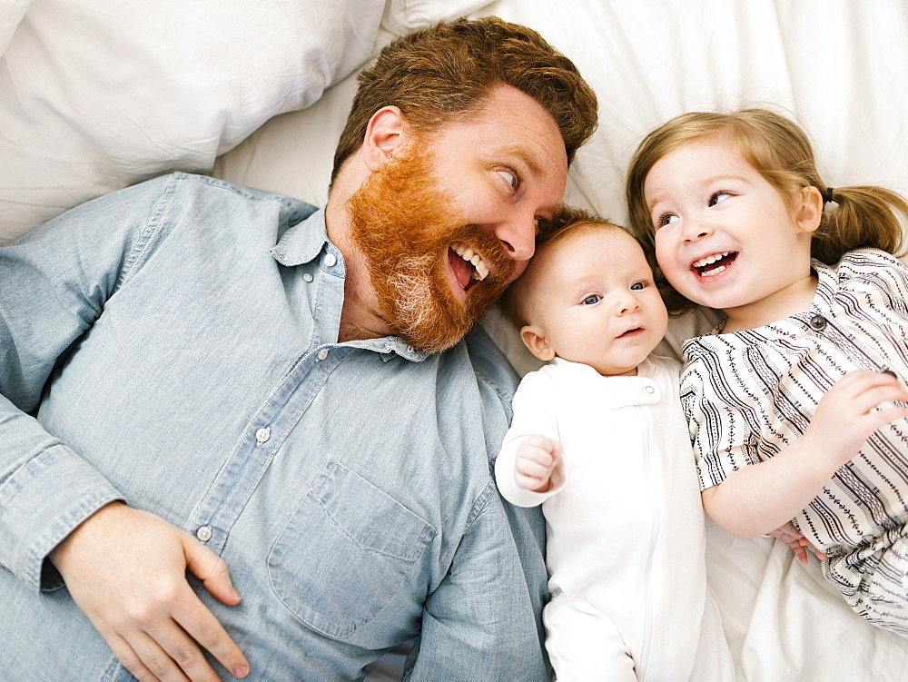 Father and children (2-3 months, 2-3) lying on bed and laughing