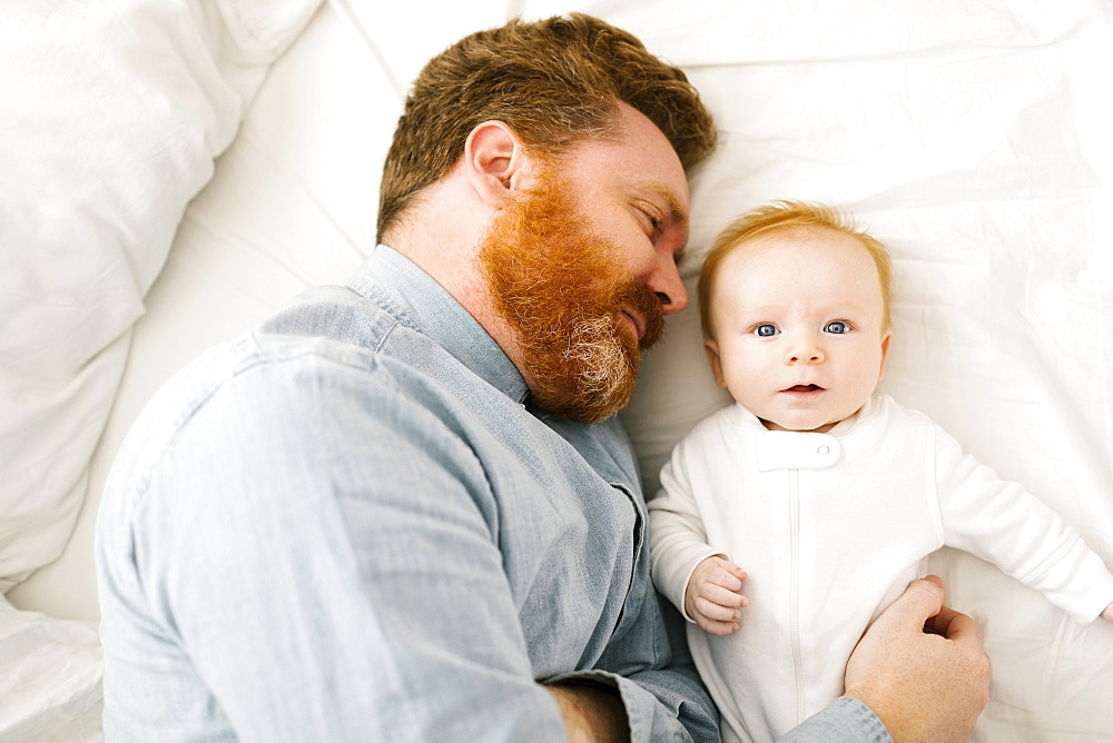 Father and baby boy (2-3 months) lying on bed