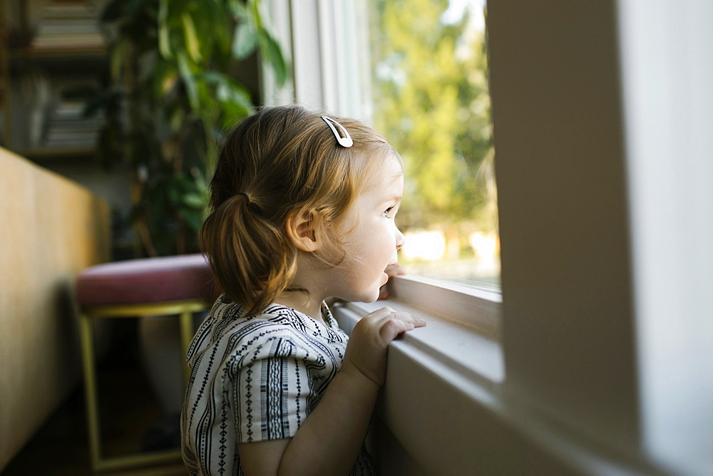 Girl (2-3) looking through window
