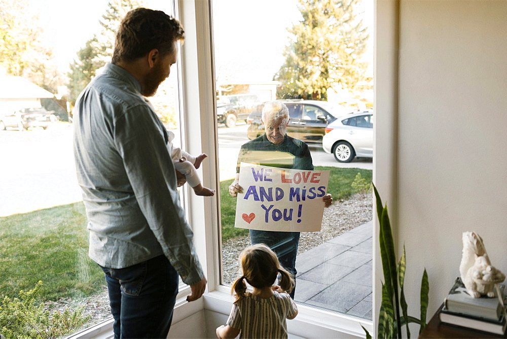 Grandfather showing message to family with grandchildren (2-3 months, 2-3) through window