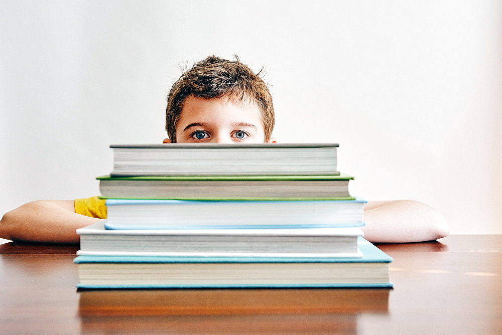 Boy behind stack of books