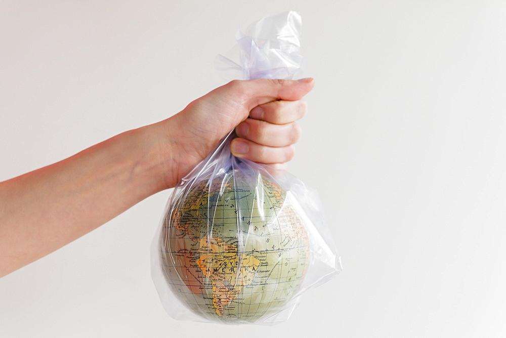 Hand holding earth globe in plastic bag