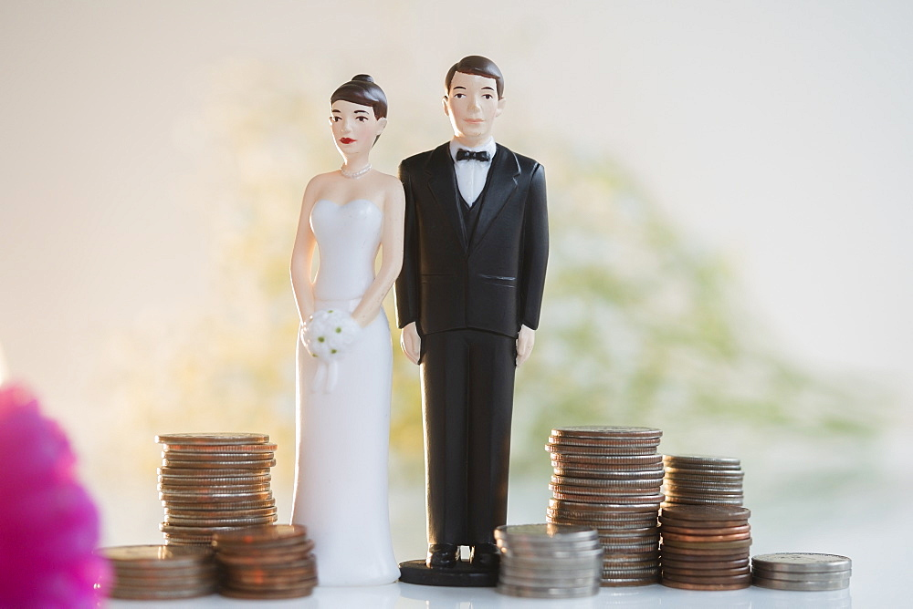 Bride and Groom cake toppers next to stacks of coins
