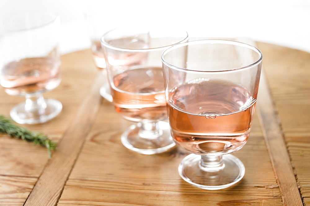 Glasses of rose wine on wooden table