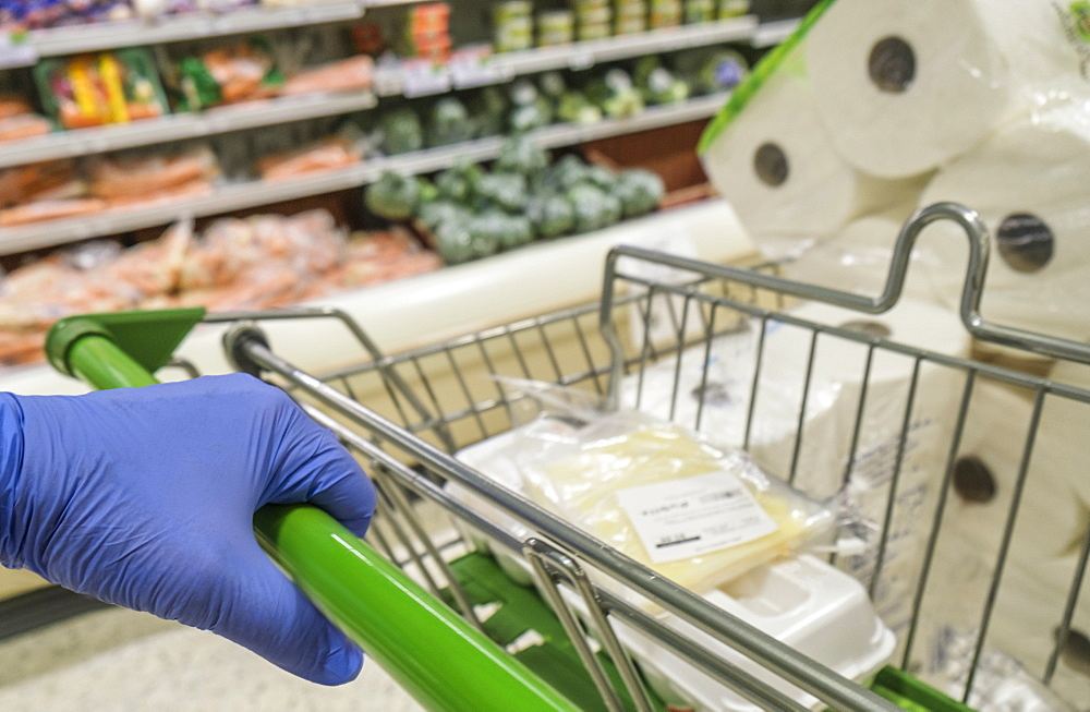 Close-up of gloved hand pushing shopping cart in grocery store
