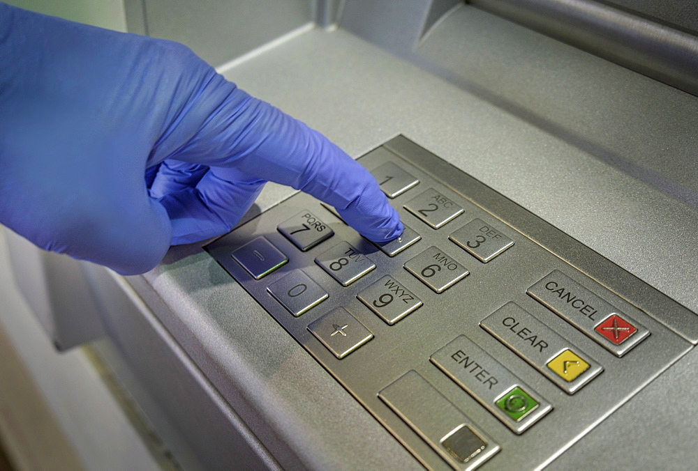 Gloved hand pushing button of cash machine