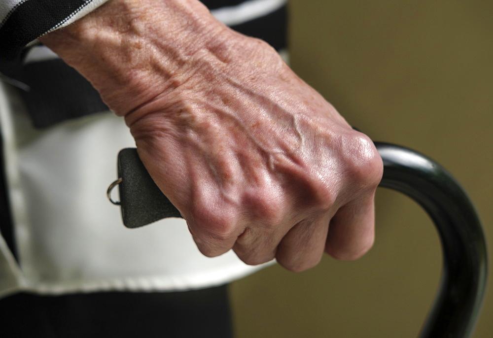 Close up of hand of senior woman holding cane
