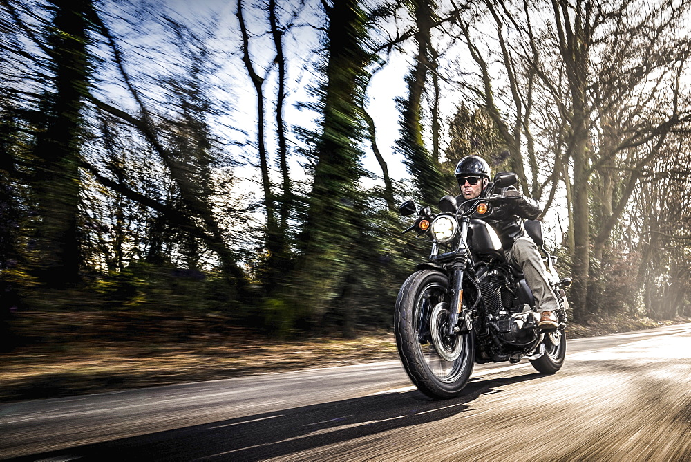 United Kingdom, London, Motorcyclist on road in forest