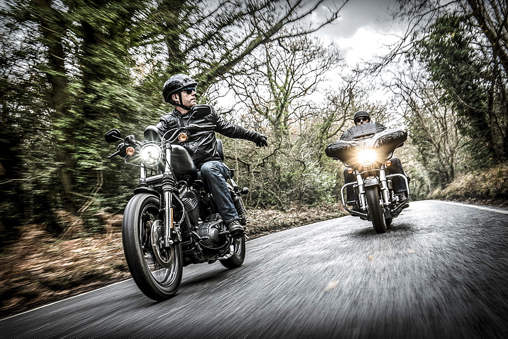 United Kingdom, London, Motorcyclists on road in forest