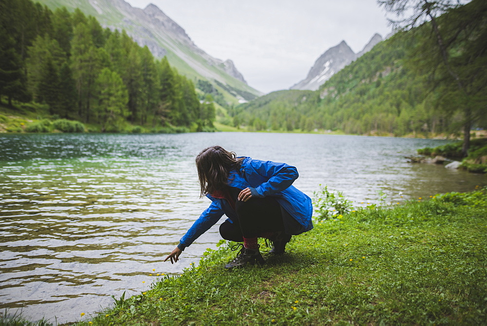 Switzerland, Bravuogn, Palpuognasee, Young woman crouching by Palpuognasee lake in Swiss Alps