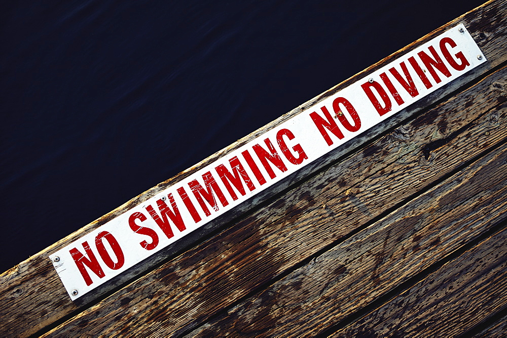 No swimming No diving sign at the edge of wooden jetty