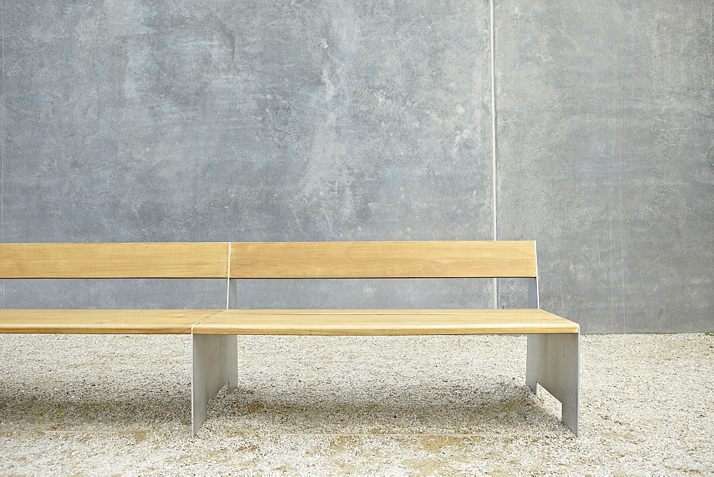 Wooden modern bench against concrete wall