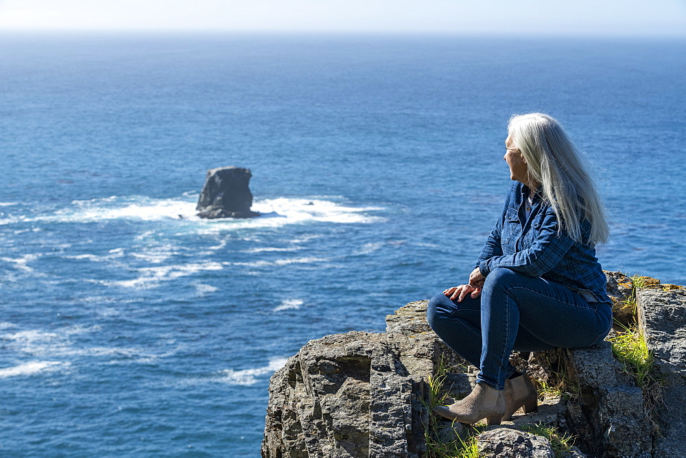USA, California, Big Sur, Woman sitting at the edge of cliff looking at view