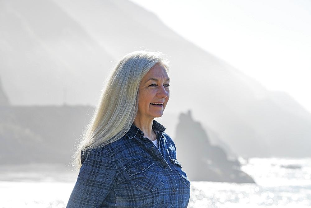 USA, California, Big Sur, Portrait of senior woman in front of cliffs