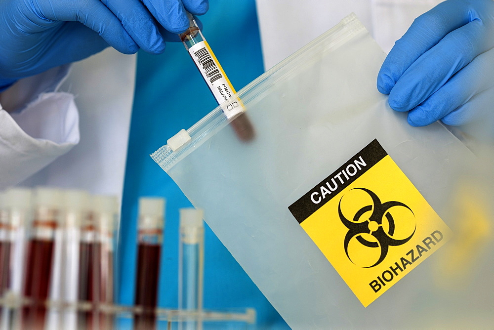 Lab professional putting vial into string bag with biohazard sign