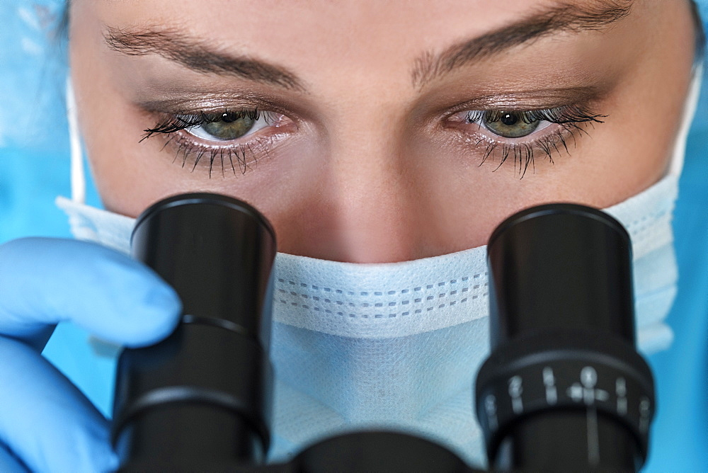 Laboratory technician in face mask looking through microscope - 1178-29723