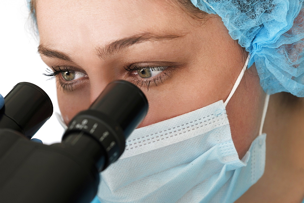 Laboratory technician in face mask looking through microscope