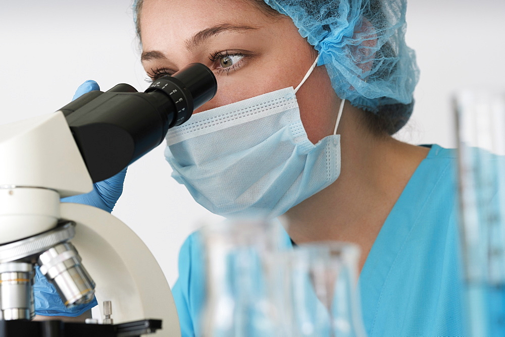 Laboratory technician in face mask looking through microscope - 1178-29727