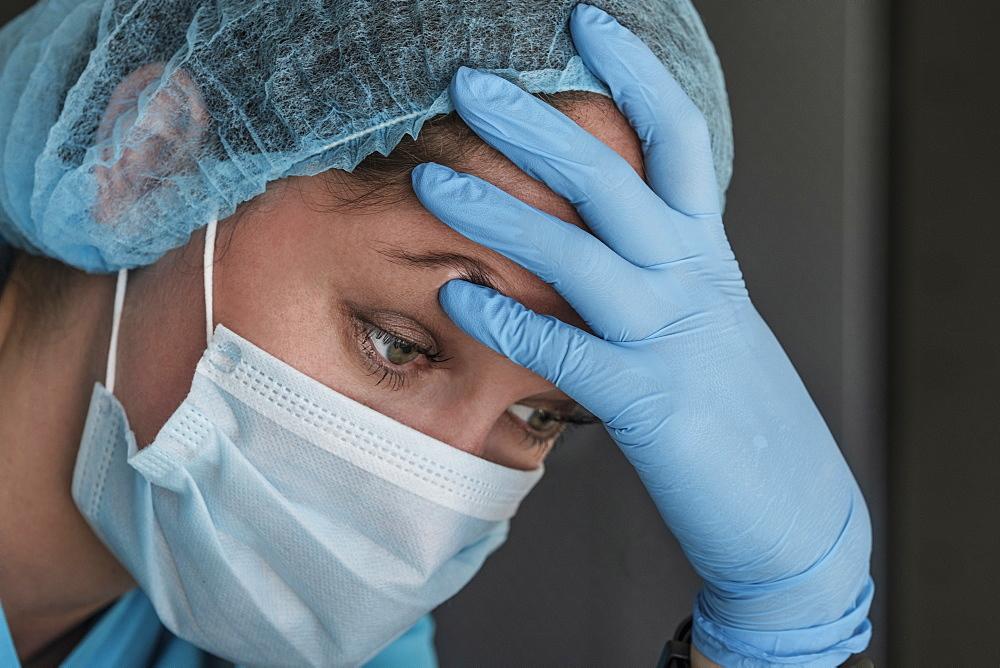 Nurse in face mask experiencing symptoms