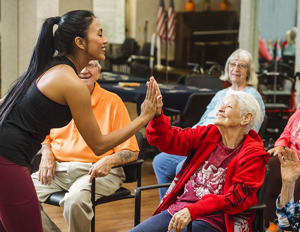 Senior woman high-fiving fitness instructor