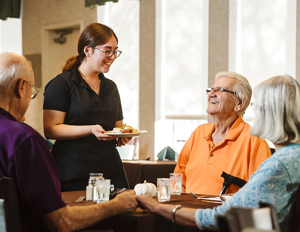 Waitress bringing meal to senior people at table