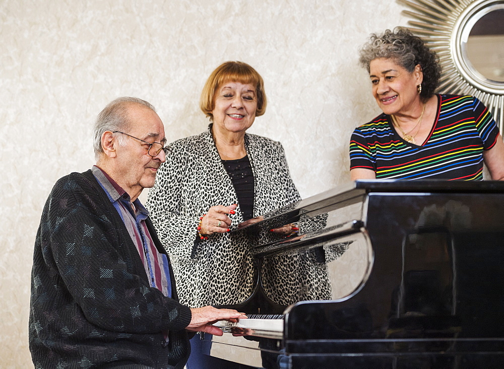 Senior women listening to man playing piano