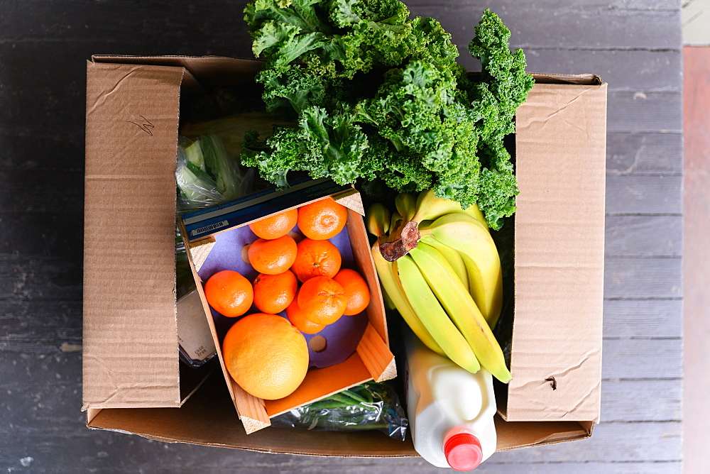 Overhead view of box of delivered produce on house porch