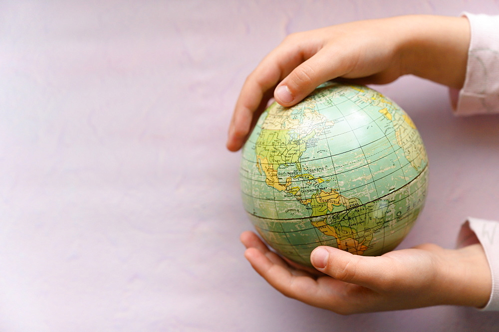 Close-up of girls (6-7) hands holding globe