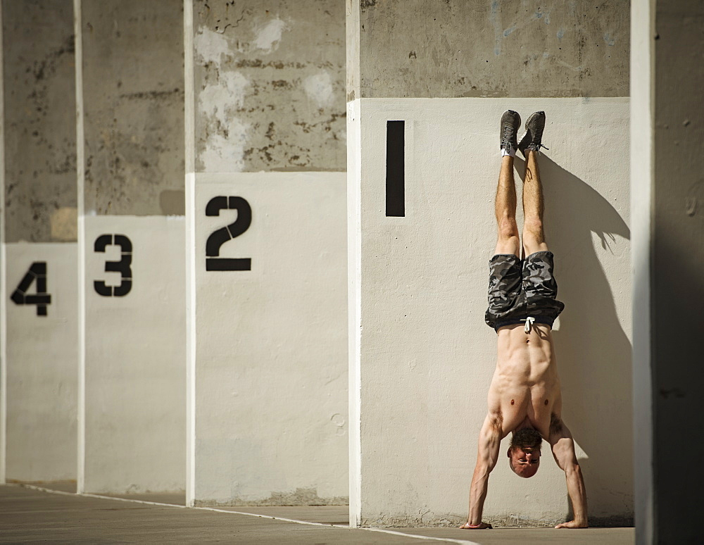 Man doing handstand next to wall