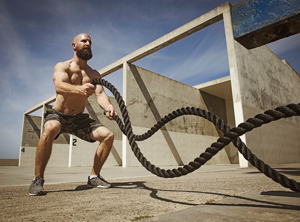 Man exercising with ropes