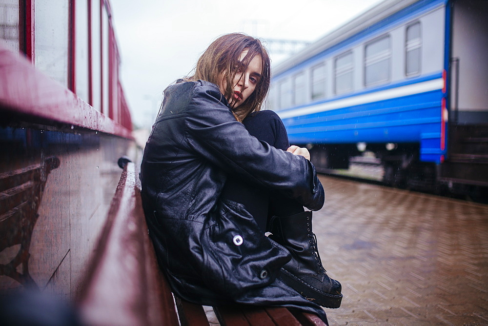 Belarus, Minsk, Young woman waiting on train platform in rain