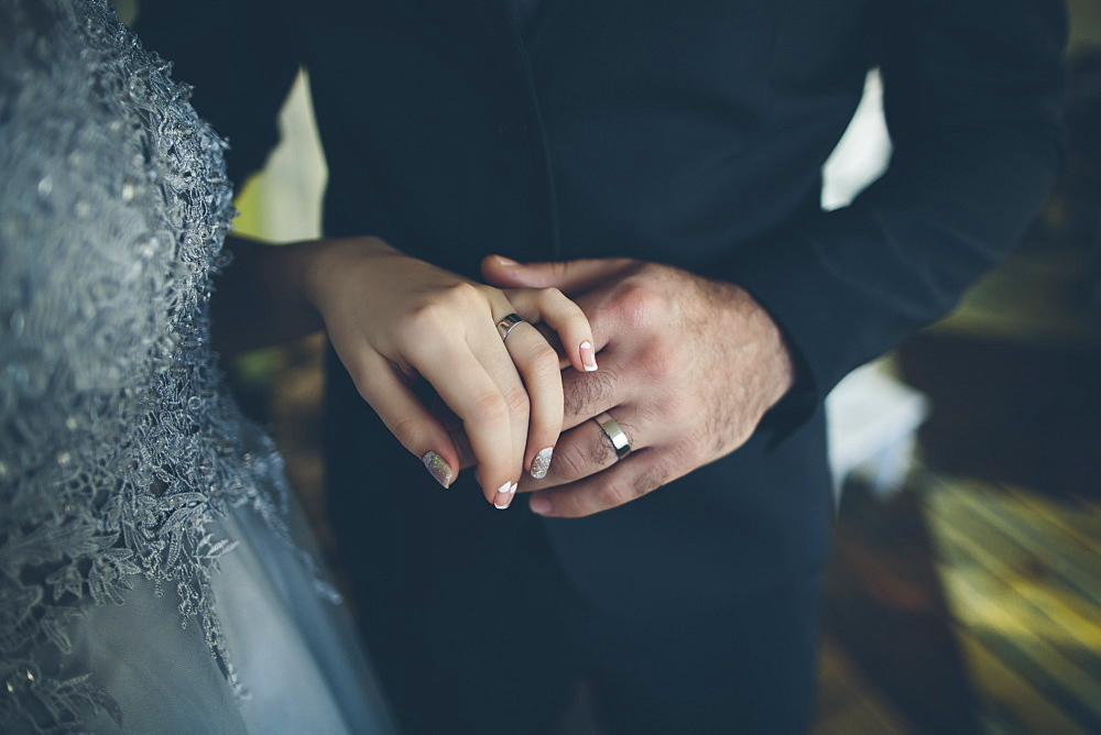 Close up of hands of bride and groom wearing wedding ring