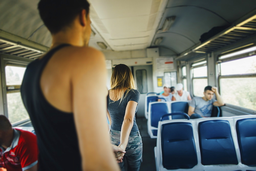 Young couple walking inside of train