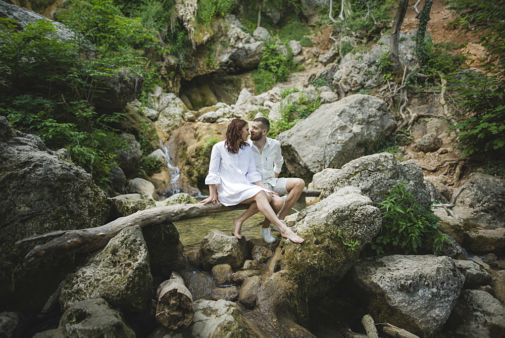 Ukraine, Crimea, Young couple sitting on branch over river in canyon