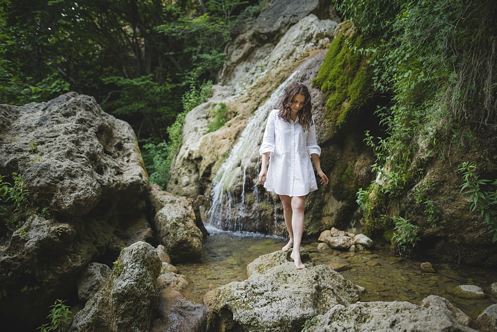Ukraine, Crimea, Young woman walking barefoot on rocks near waterfall