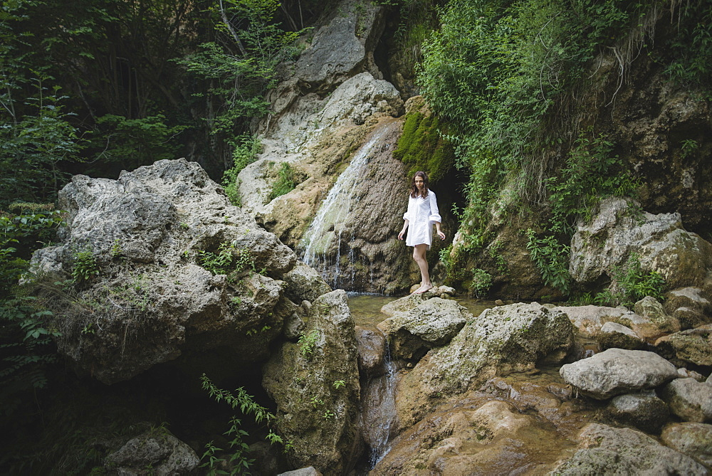 Ukraine, Crimea, Young woman walking barefoot on rocks in canyon
