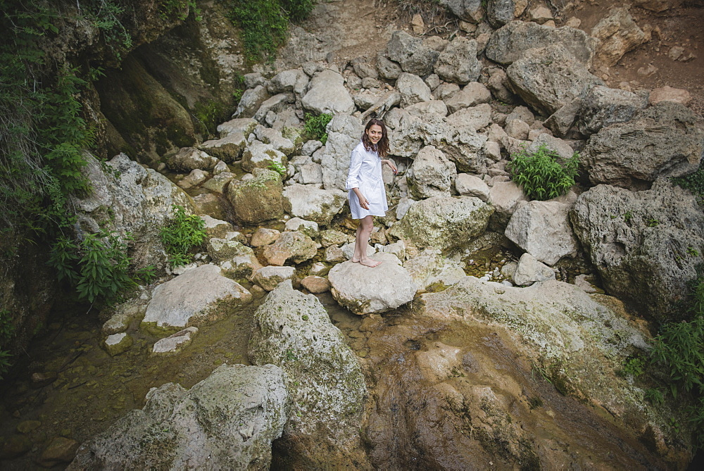 Ukraine, Crimea, Young woman standing on rock in river