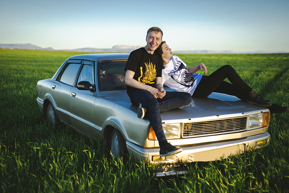 Ukraine, Crimea, Couple sitting on old fashioned car in rural scenery