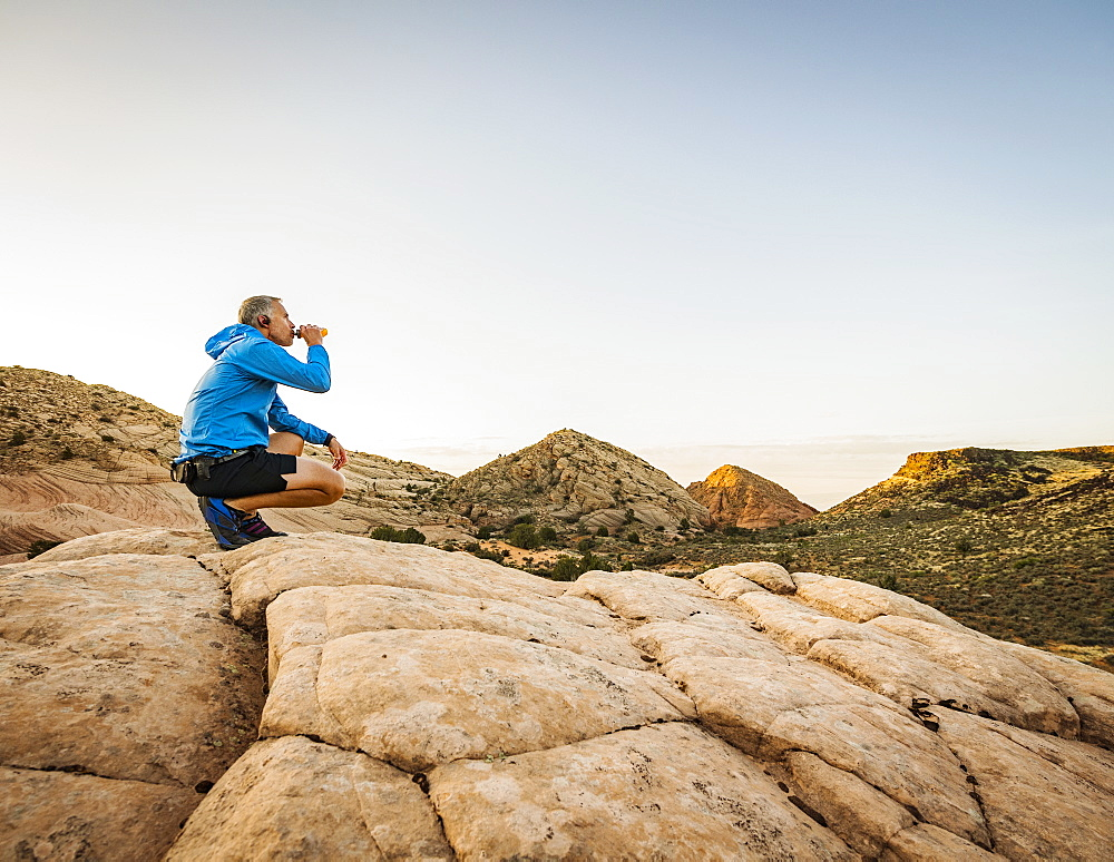 USA, Utah, St. George, Man crouching in rocky landscape and drinking water after running