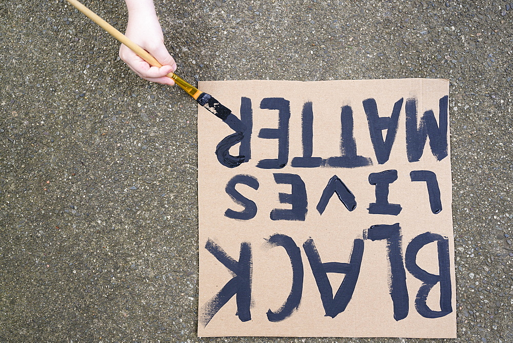 Woman's hand painting Black Lives Matter sign on cardboard - 1178-30028