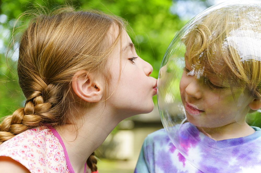 Girl kissing boy wearing bubble to socially distance - 1178-30031