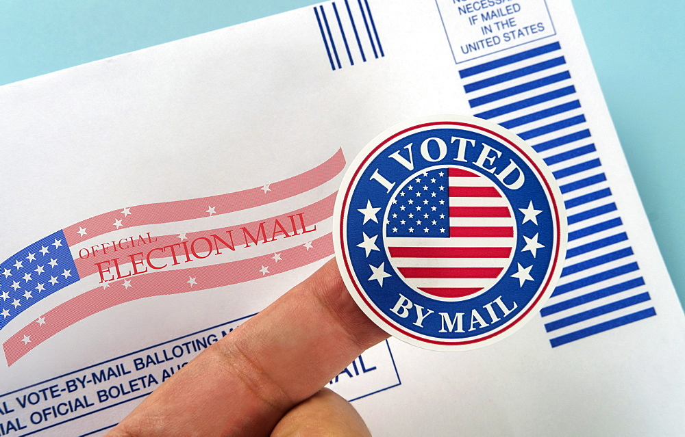 Human finger holding sticker above voting mail - 1178-30036